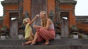 Φορητός πυροβολισμός μιας νέας γυναίκας και της συνεδρίασης γιων της στα σκαλοπάτια του ναού Taman Ayun στο νησί του Μπαλί φιλμ μικρού μήκους