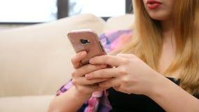 Φορητός πυροβολισμός της unrecognisable γυναίκας που χρησιμοποιεί το smartphone της στον καναπέ απόθεμα βίντεο