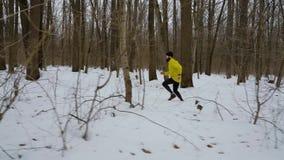 Φορητός πυροβολισμός του αθλητή που τρέχει στο χιόνι μεταξύ των δέντρων στο χειμερινό δάσος απόθεμα βίντεο