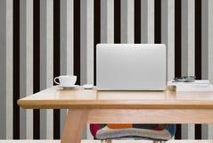 Φορητός υπολογιστής και ένα φλιτζάνι του καφέ στο λειτουργώντας πίνακα στο στούντιο στοκ φωτογραφία με δικαίωμα ελεύθερης χρήσης