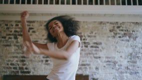 Φορητό του χαρούμενου αφροαμερικάνου teeanger το κορίτσι έχει τη διασκέδαση χορεύοντας κοντά στο κρεβάτι στο σπίτι φιλμ μικρού μήκους