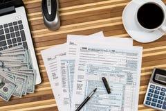 Φορολογική μορφή με τον καφέ, το lap-top, τη μάνδρα και τον υπολογιστή Στοκ Φωτογραφίες