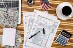 Φορολογική μορφή με τον καφέ, το lap-top, τον υπολογιστή μανδρών και το δολάριο Στοκ φωτογραφία με δικαίωμα ελεύθερης χρήσης
