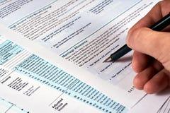 φορολογική υποβολή έκθεσης Ο άνθρωπος συμπληρώνει το φορολογικό έντυπο στοκ φωτογραφίες με δικαίωμα ελεύθερης χρήσης