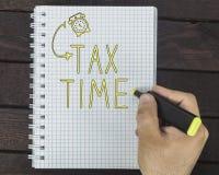 Φορολογικός χρόνος γραψίματος χεριών στο σημειωματάριο στο σκοτεινό ξύλινο γραφείο Στοκ εικόνες με δικαίωμα ελεύθερης χρήσης