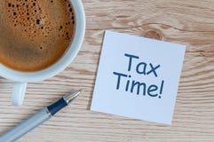 φορολογικός χρόνος Εργασιακός χώρος με το φλυτζάνι καφέ πρωινού, και ανακοίνωση για τους φόρους Στοκ φωτογραφία με δικαίωμα ελεύθερης χρήσης