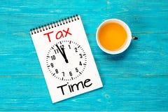 Φορολογικός χρόνος, μήνυμα με το ρολόι στο σημειωματάριο πέρα από τον τυρκουάζ πίνακα Στοκ εικόνες με δικαίωμα ελεύθερης χρήσης
