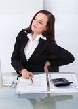 Φορολογικός σύμβουλος που πάσχει από τον πόνο στην πλάτη στο γραφείο Στοκ εικόνες με δικαίωμα ελεύθερης χρήσης