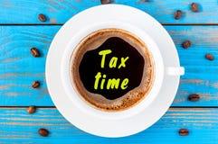 Φορολογικός χρόνος που γράφεται αντιμετωπισμένο στο κορυφή φλυτζάνι καφέ πρωινού χρυσή ιδιοκτησία βασικών πλήκτρων επιχειρησιακής Στοκ Φωτογραφία