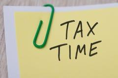 Φορολογικός χρόνος που γράφεται στην κίτρινη σημείωση Στοκ εικόνες με δικαίωμα ελεύθερης χρήσης