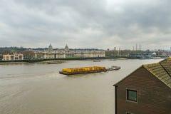 Φορτηγίδα που τραβά τα κίτρινα εμπορευματοκιβώτια στον ποταμό Τάμεσης και που περνά μέσω του Γκρήνουιτς Στοκ Εικόνες