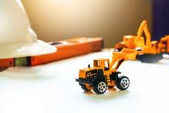 Φορτηγό αυτοκινήτων παιχνιδιών του μηχανικού που λειτουργεί στον πίνακα γραφείων εφαρμοσμένης μηχανικής με Στοκ Φωτογραφία