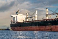 Φορτηγό πλοίο που ελλιμενίζεται με τη βάρκα ρυμουλκών στοκ εικόνες με δικαίωμα ελεύθερης χρήσης