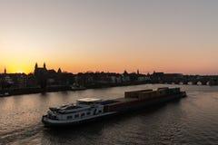 Φορτηγό πλοίο που φορτώνεται με τα εμπορευματοκιβώτια που ταξιδεύουν πέρα από τον ποταμό Maas στοκ εικόνες