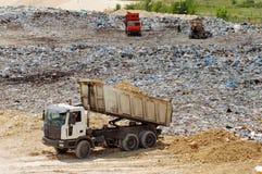 Φορτηγό που λειτουργεί στα υλικά οδόστρωσης με τα πουλιά που ψάχνουν τα τρόφιμα Απορρίματα στην απόρριψη πόλεων Εδαφολογική ρύπαν Στοκ εικόνα με δικαίωμα ελεύθερης χρήσης