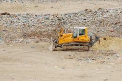 Φορτηγό που λειτουργεί στα υλικά οδόστρωσης με τα πουλιά που ψάχνουν τα τρόφιμα Απορρίματα στην απόρριψη πόλεων Εδαφολογική ρύπαν Στοκ φωτογραφίες με δικαίωμα ελεύθερης χρήσης
