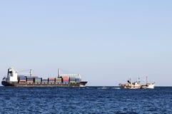 Φορτηγό πλοίο και μικρή αναχώρηση βαρκών αλιευτικών πλοιαρίων στοκ φωτογραφίες με δικαίωμα ελεύθερης χρήσης