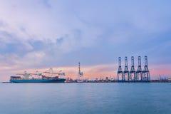 Φορτηγό πλοίο στον εμπορικό λιμένα, φόρτωση εμπορευματοκιβωτίων που στέλνει από το γερανό Στοκ φωτογραφία με δικαίωμα ελεύθερης χρήσης