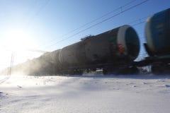 Φορτηγό τρένο με τις δεξαμενές πετρελαίου στην κίνηση Μύγες σκόνης χιονιού από ένα περνώντας τραίνο με υψηλή ταχύτητα Παγωμένη ηλ στοκ εικόνα