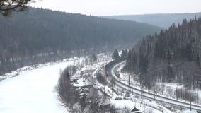 Φορτηγό τρένο που κινείται μέσω του κωνοφόρου δάσους κατά τη διάρκεια των χιονοπτώσεων κατά μήκος του παγωμένου ποταμού απόθεμα βίντεο