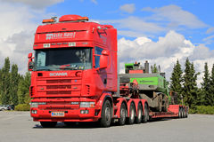 Φορτηγό Scania 164G 480 που μεταφέρει τη μηχανή υλικού χειρισμού Στοκ Φωτογραφίες