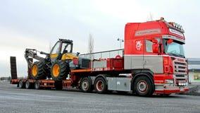 Φορτηγό Scania R500 που μεταφέρει μια δασική θεριστική μηχανή Στοκ Εικόνες
