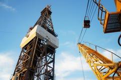 Φορτωτήρας του γρύλου επάνω στην εγκατάσταση γεώτρησης γεώτρησης πετρελαίου και το γερανό εγκαταστάσεων γεώτρησης Στοκ Φωτογραφία