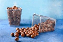 Φουντούκι που διασκορπίζεται στον πίνακα όμορφο μπλε ανασκόπησης Καρύδια στα καλάθια Στοκ φωτογραφία με δικαίωμα ελεύθερης χρήσης