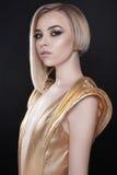 Φουτουριστική προκλητική γυναίκα στο χρυσό φόρεμα Στοκ Εικόνες