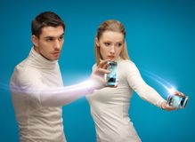 Φουτουριστικοί άνδρας και γυναίκα που εργάζονται με τις συσκευές Στοκ Εικόνες