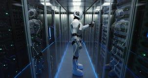 Φουτουριστικό αρρενωπό ρομπότ που λειτουργεί στο δωμάτιο κεντρικών υπολογιστών στοκ εικόνες