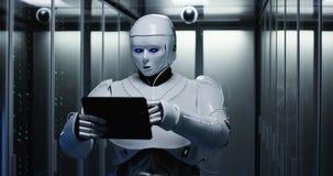 Φουτουριστικό ρομπότ με την ταμπλέτα στο δωμάτιο κεντρικών υπολογιστών στοκ εικόνες