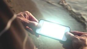 Φουτουριστικό smartphone πυράκτωσης που το άτομο στην παραλία - έννοια τεχνολογίας απόθεμα βίντεο