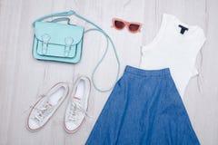 Φούστα τζιν, γυαλιά, άσπρα πάνινα παπούτσια, τσάντα και κορυφή μοντέρνη έννοια Ξύλινη ανασκόπηση Στοκ φωτογραφία με δικαίωμα ελεύθερης χρήσης