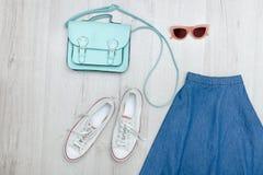 Φούστα τζιν, γυαλιά, άσπρες πάνινα παπούτσια και τσάντα Μοντέρνος ομο Στοκ Φωτογραφίες