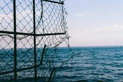 Φράκτης από το πλέγμα ενάντια στη θάλασσα Στοκ φωτογραφία με δικαίωμα ελεύθερης χρήσης