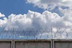 Φράκτης με οδοντωτό - καλώδιο στο υπόβαθρο των σύννεφων Στοκ Φωτογραφία