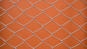 Φράκτης με τον πορτοκαλή συμπαγή τοίχο Στοκ Εικόνα
