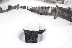 Φράκτης πίσω αυλών και δοχείο απορριμμάτων στη χιονοθύελλα Στοκ εικόνα με δικαίωμα ελεύθερης χρήσης