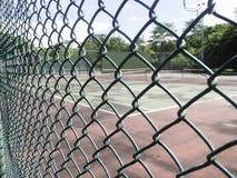Φράκτης συνδέσεων αλυσίδων με το υπόβαθρο γηπέδων αντισφαίρισης στοκ εικόνες