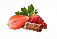 Φράουλα, ολόκληρος και διχοτομημένος με πράσινα φύλλα και τρία ραβδιά κανέλας στοκ φωτογραφία με δικαίωμα ελεύθερης χρήσης