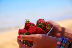 Φράουλα στη θηλυκή κινηματογράφηση σε πρώτο πλάνο χεριών στο θολωμένο υπόβαθρο Στοκ Εικόνες