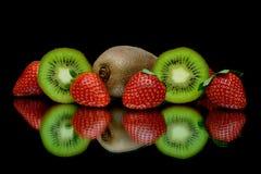 Φράουλες και ακτινίδιο σε μια μαύρη ανασκόπηση με την αντανάκλαση Στοκ φωτογραφία με δικαίωμα ελεύθερης χρήσης