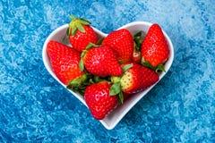 Φράουλες σε ένα άσπρο καρδιά-διαμορφωμένο πιάτο στοκ εικόνες