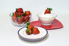 Φράουλες σε ένα κύπελλο, στην κτυπημένη κρέμα και στα πιάτα στοκ εικόνες