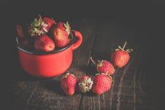 Φράουλες σε μια κούπα σιδήρου σε έναν ξύλινο πίνακα Στοκ Φωτογραφίες