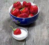 Φράουλα πιάτων και μια φράουλα σε ένα πιατάκι με την κρέμα Στοκ εικόνες με δικαίωμα ελεύθερης χρήσης