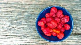 Φράουλα σε ένα κύπελλο με το ξύλινο υπόβαθρο Στοκ Φωτογραφίες