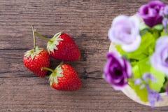 Φράουλα στον ξύλινο πίνακα με το ντεκόρ λουλουδιών Στοκ φωτογραφία με δικαίωμα ελεύθερης χρήσης
