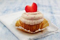 Φράουλα Cupcakes με το πάγωμα φραουλών και τις φρέσκες καρδιές φραουλών Στοκ Φωτογραφίες